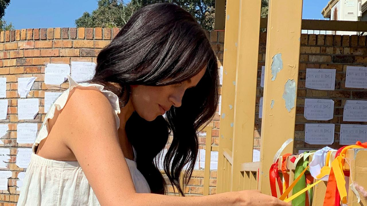 Meghan, Duchess of Sussex, ties on a ribbon at the memorial to murdered South African student Uyinene Mrwetyana in Cape Town.