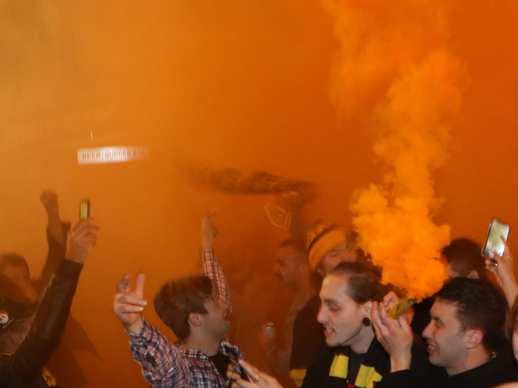 Flares are set off on Swan Street as Tigers fans celebrate.