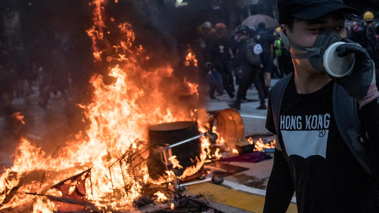 A pro-democracy protester walks in front of a burning barricade during clashes with police on Tuesday. Picture: Chris McGrath/Getty Images.