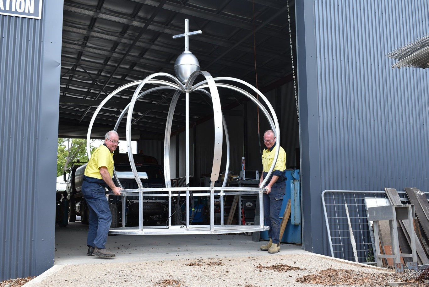 Electrician John Hough and Tony Blackadder from Grafton Ally Fabrications put the finishing touches to the new Jacaranda Queen Clocktower crown.