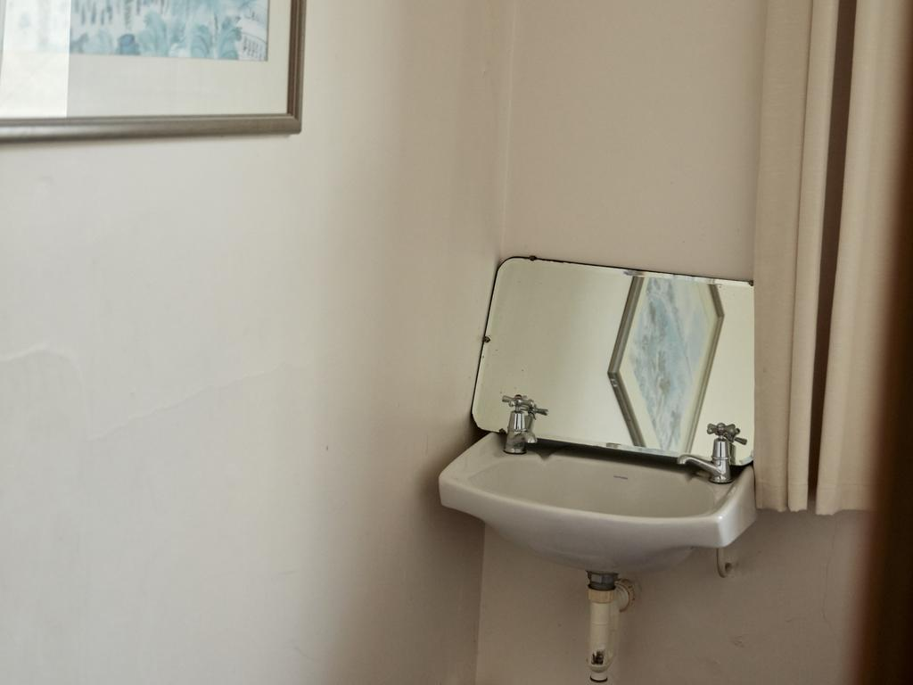A drab bathroom at the Royal Standard Hotel before the renovation. Picture: Airbnb