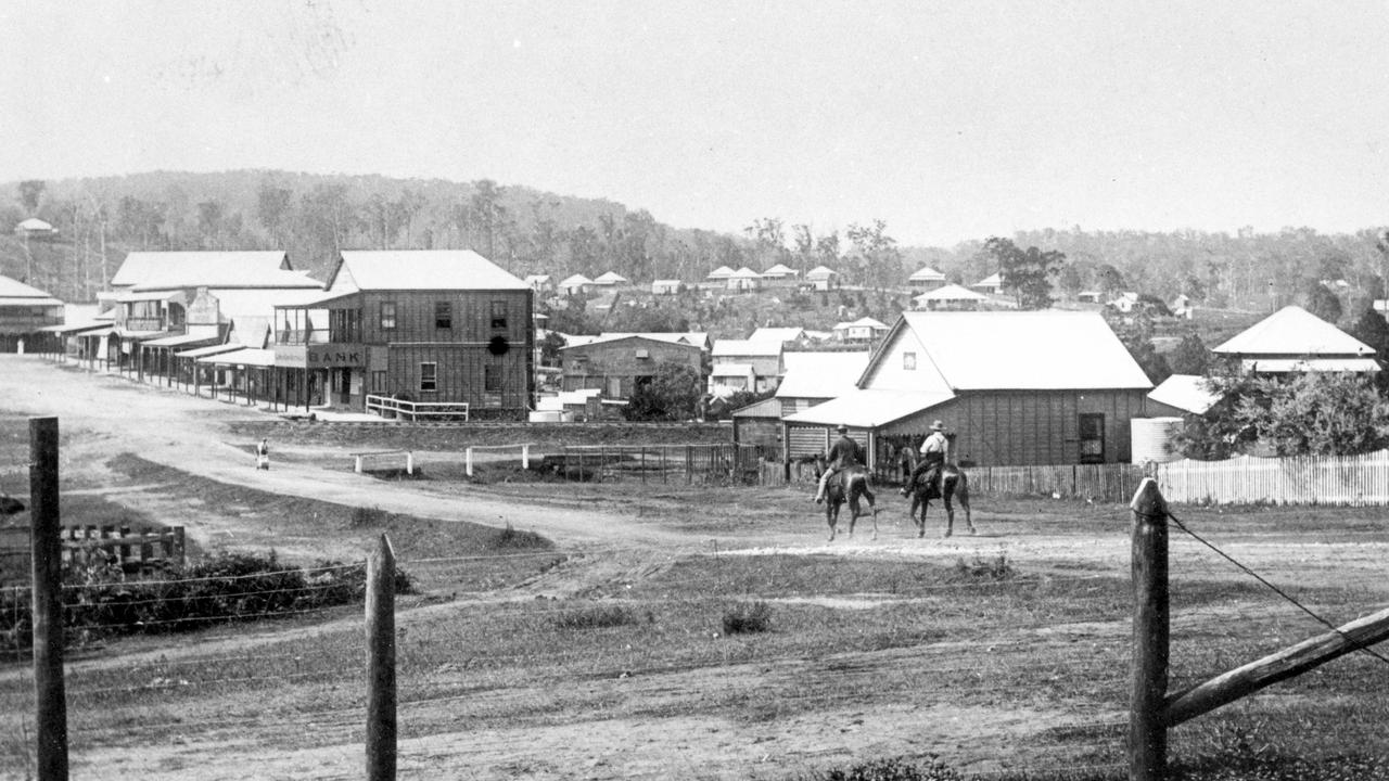 Currie Street, Nambour, looking north from the corner of Bury Street, ca 1915. Bury Street intersection in foreground, two-storey E.S. & A. Bank in middle distance (on the eastern side of Currie Street).Two horsemen passing the building which originally housed the Chronicle Office.