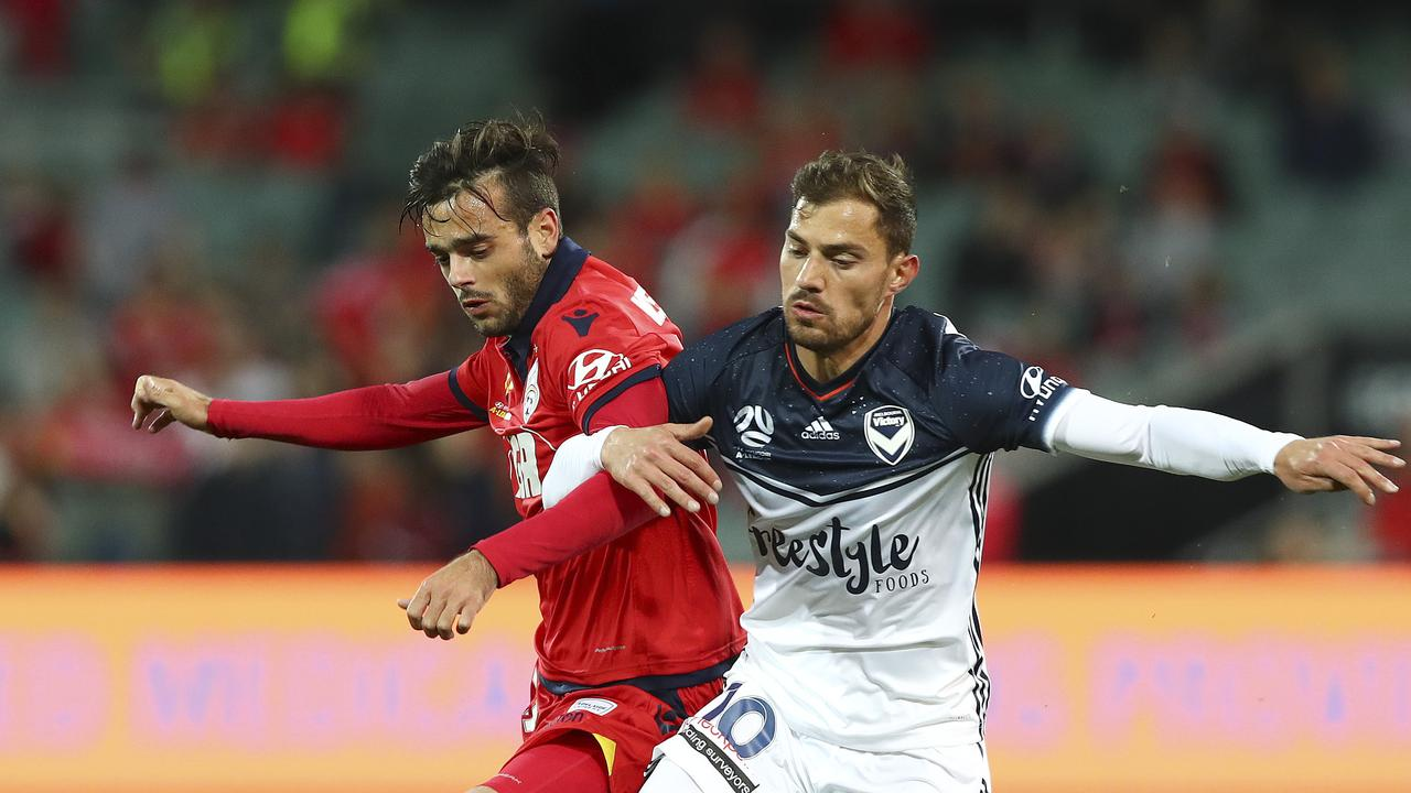 Now teammates. Adelaide United's Nikola Mileusnic links arms with his new teammate, former Melbourne Victory attacker James Troisi. Picture Sarah Reed
