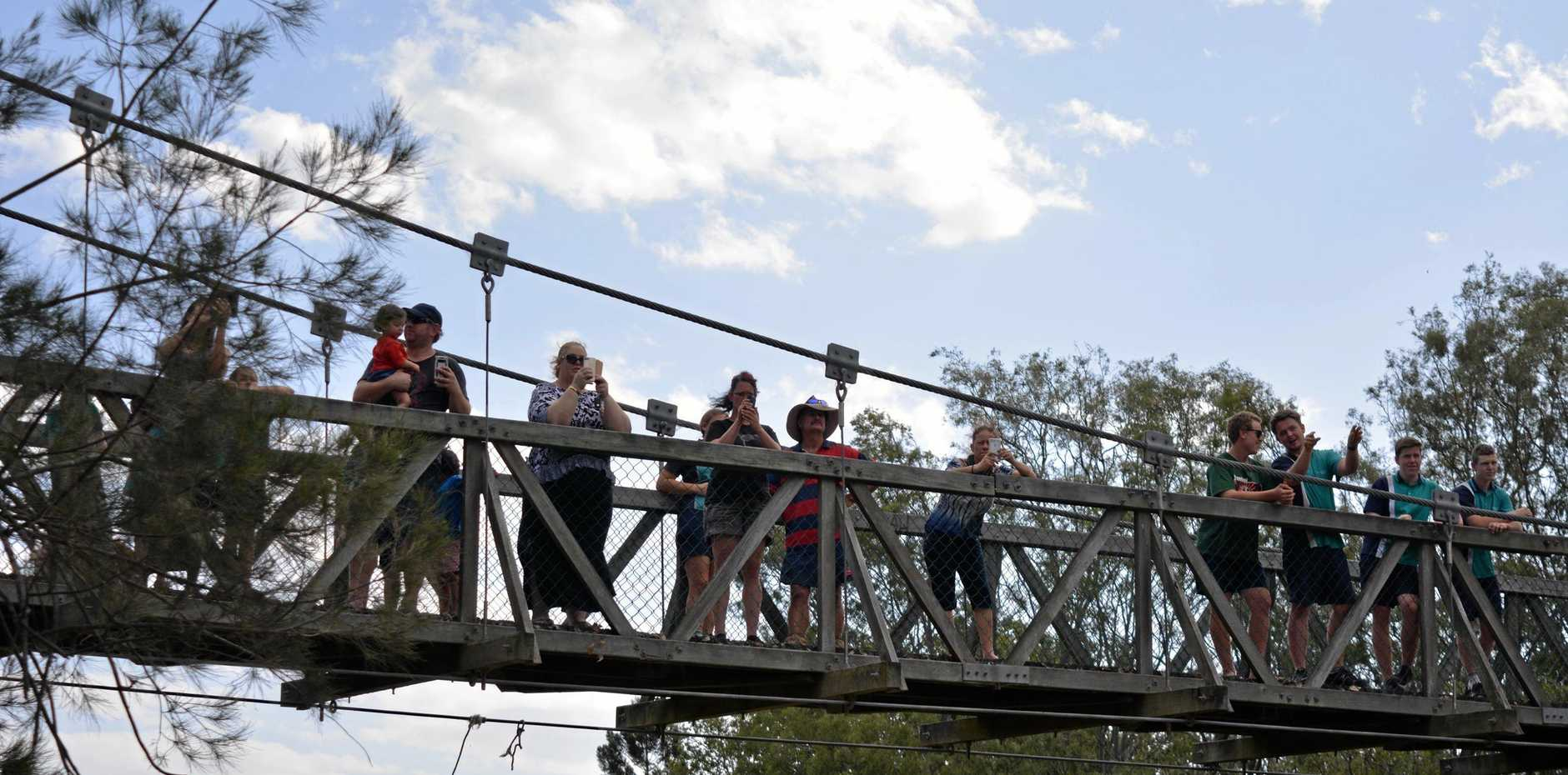 Laidley residents watch from the Nada Lagoon bridge as helicopters fill up with water to battle the Laidley fires.