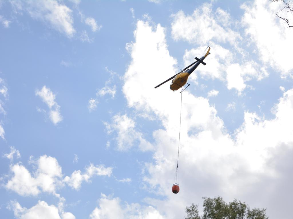 A helicopter prepares to water-drop over the blaze. Picture: Ebony Graveur