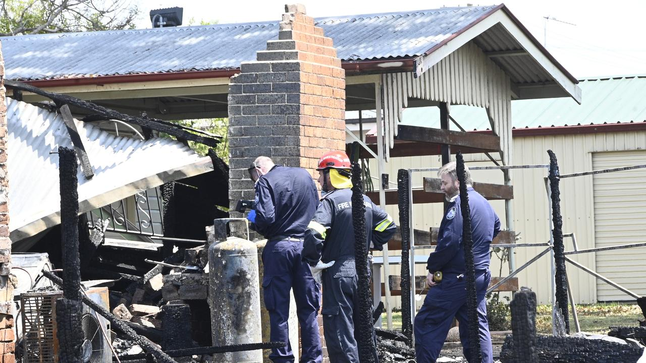 QPS and QFES fire investigators sort through the remains at the two homes in Victor Street.