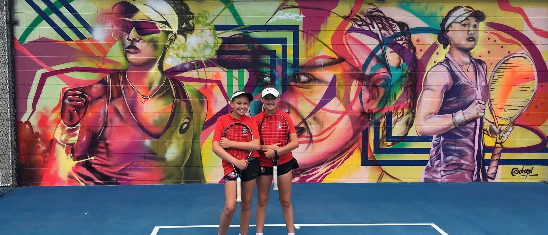 Kelvin Grove State High School tennis players Nicola Schoeman, left and Ella Pittendreigh at the unveiling of murals for Sam Stosur and Ashleigh Barty.