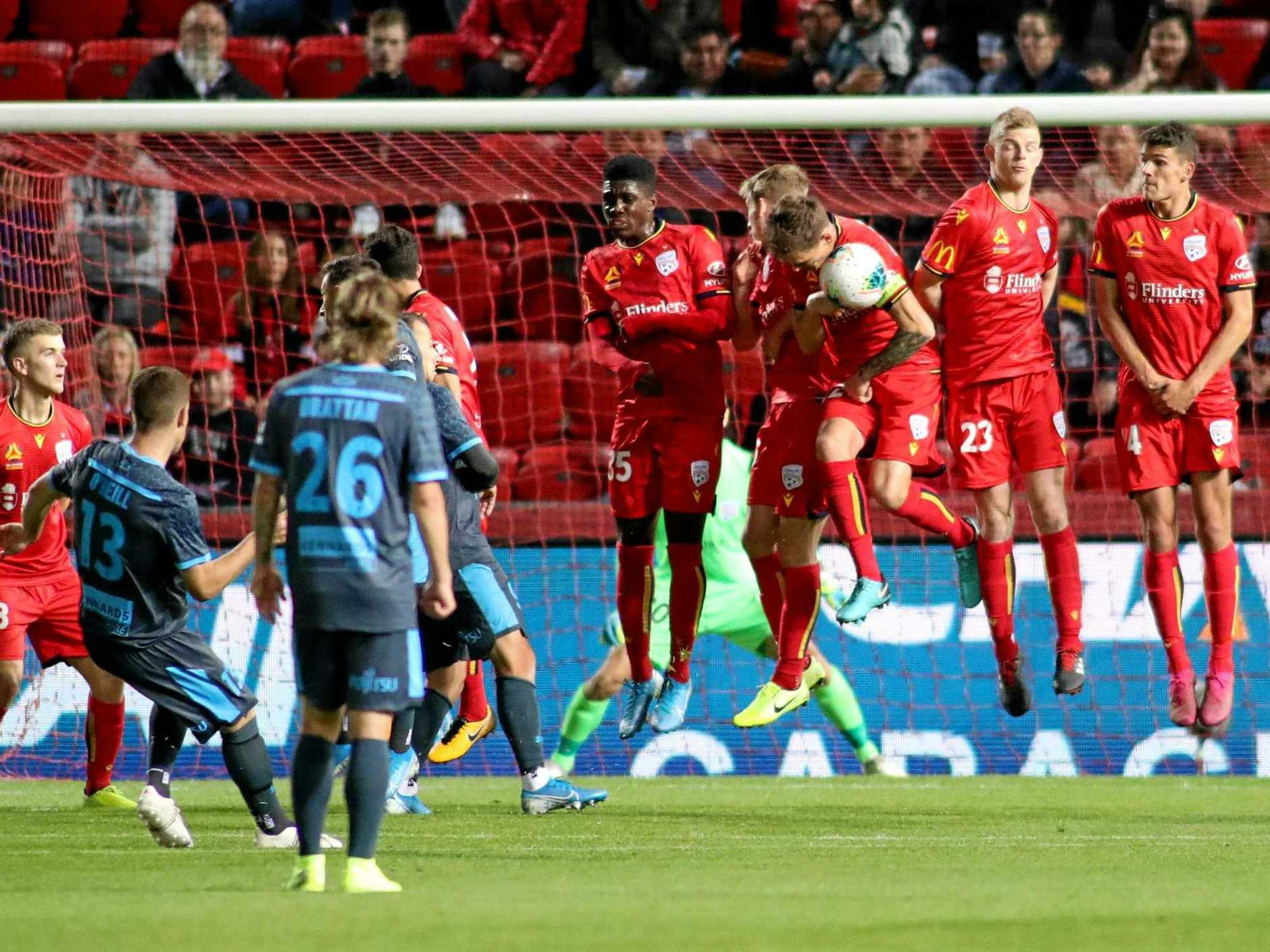 Adelaide United players stop a Sydney FC penalty shot at goal at Adelaide's Coopers Stadium on Friday night. Picture: Kelly Barnes/AAP
