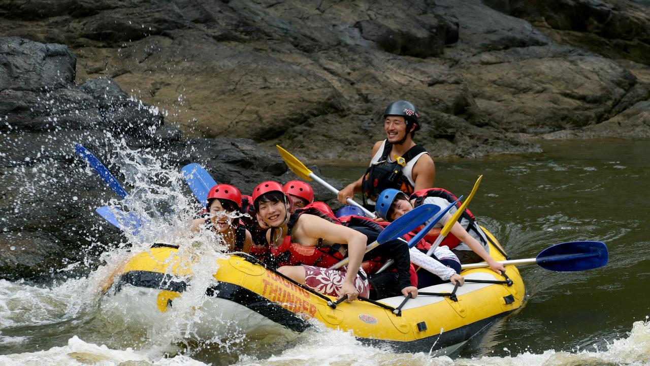 Rafting guide Tsuyoshi Fujimoto paddles down the rapids on the Barron River as heavy rain increases the flow making for a more exciting ride for the Japanese tourists white water rafters on board Raging Thunder Adventures. Picture: Marc McCormack