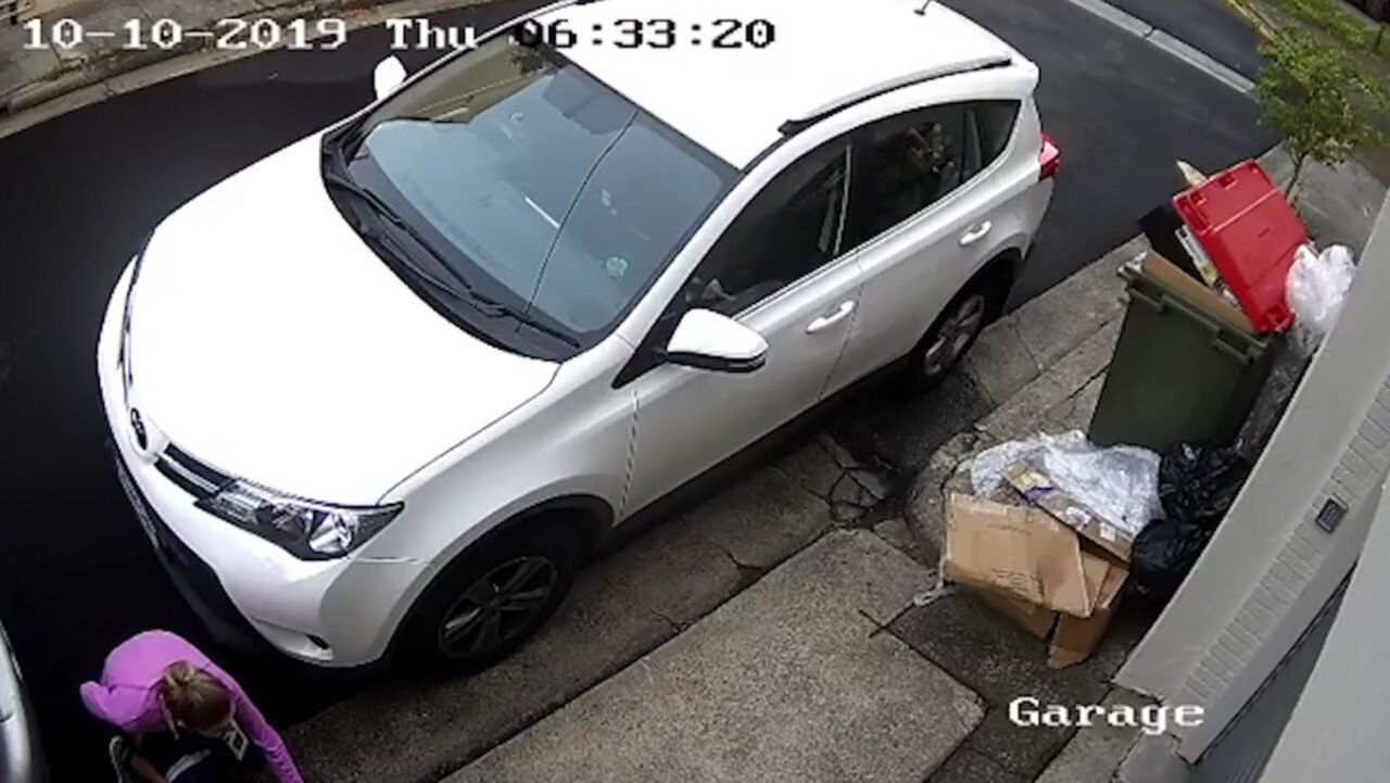 CCTV shows the woman crouching down between two parked cars to poop.