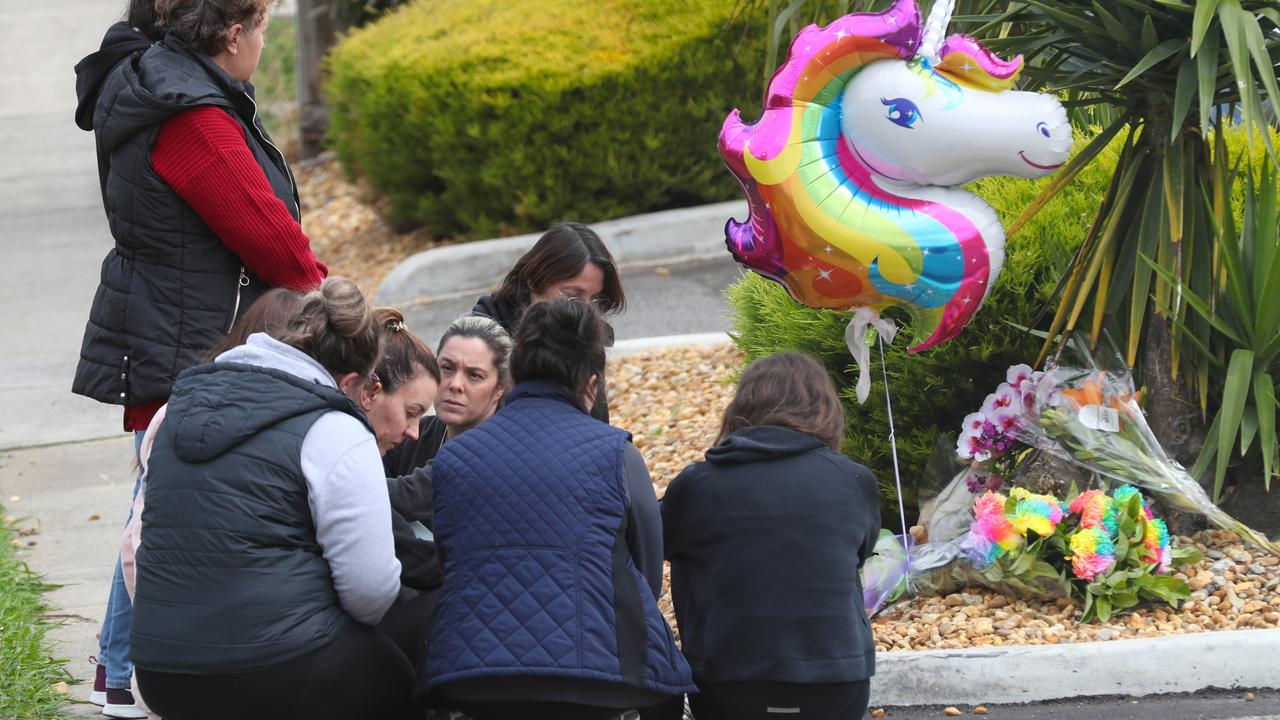 Staff of the childcare centre gather to reflect at a makeshift memorial in front of the centre. Picture: David Crosling