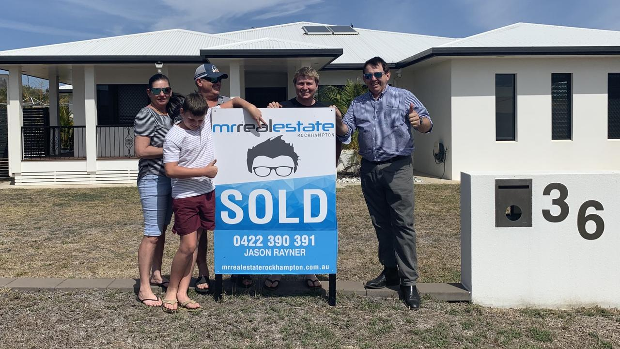 HAPPY DAYS: Stephen and Kim Smoothy with their children and Mr Real Estate Jason Rayner (right) in front of their new home.