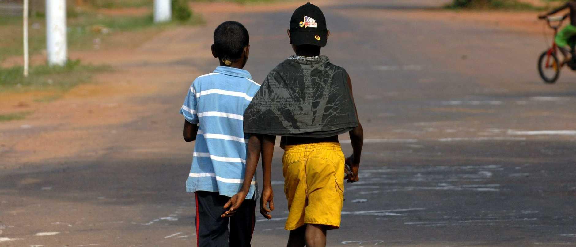 Two indigenous children walking along a street in Arukun, Queensland.
