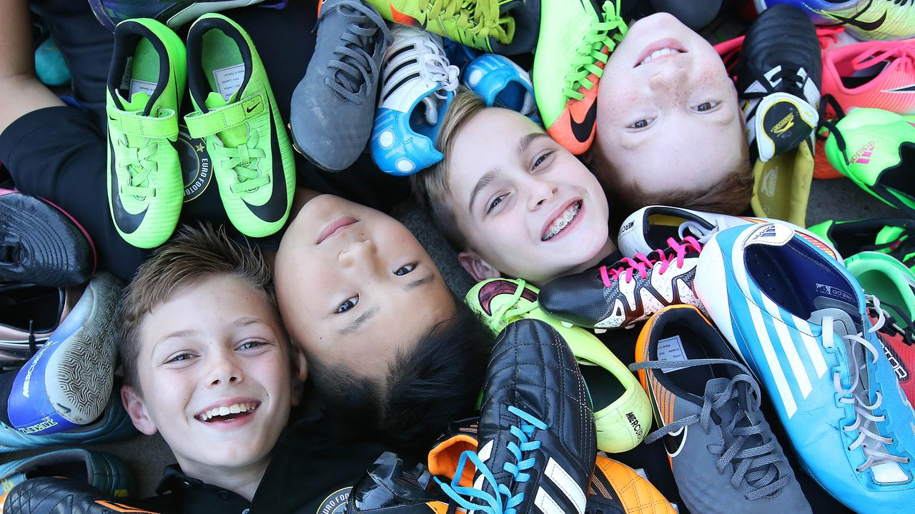 Top young football players Phoenix Thatcher, Musa Tanudjaja, Elijah Barwick and Bryn Richards with some of the boots they are collecting to send to Ghana. Picture: AAP/Jono Searle