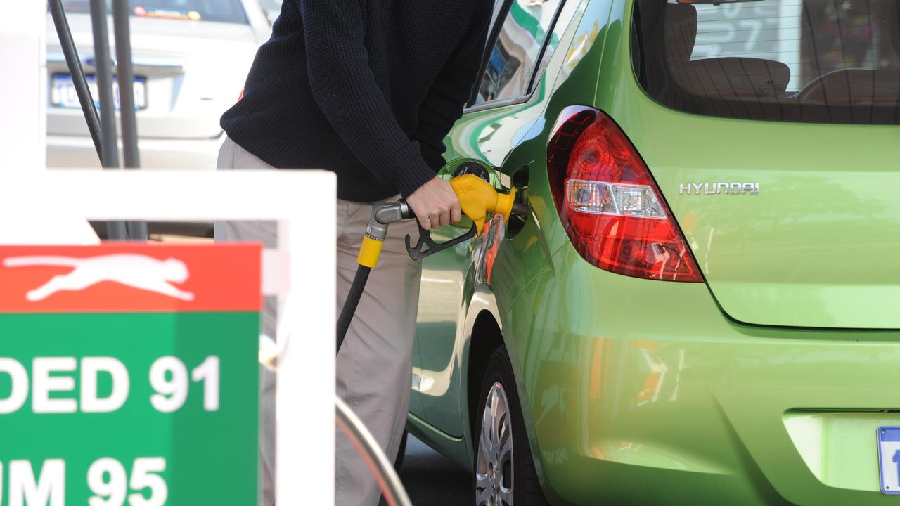 Man putting fuel into car at Puma Super 7 Service Station.
