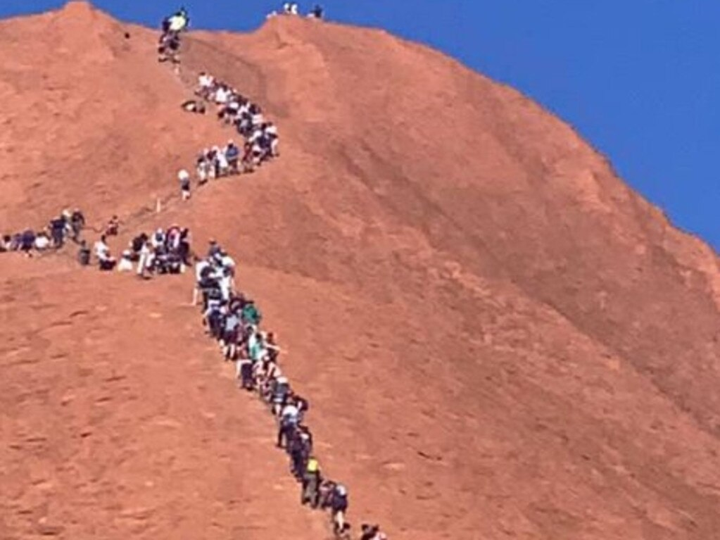 A huge line of tourists climbing up Uluru. Picture: Glenn Minett
