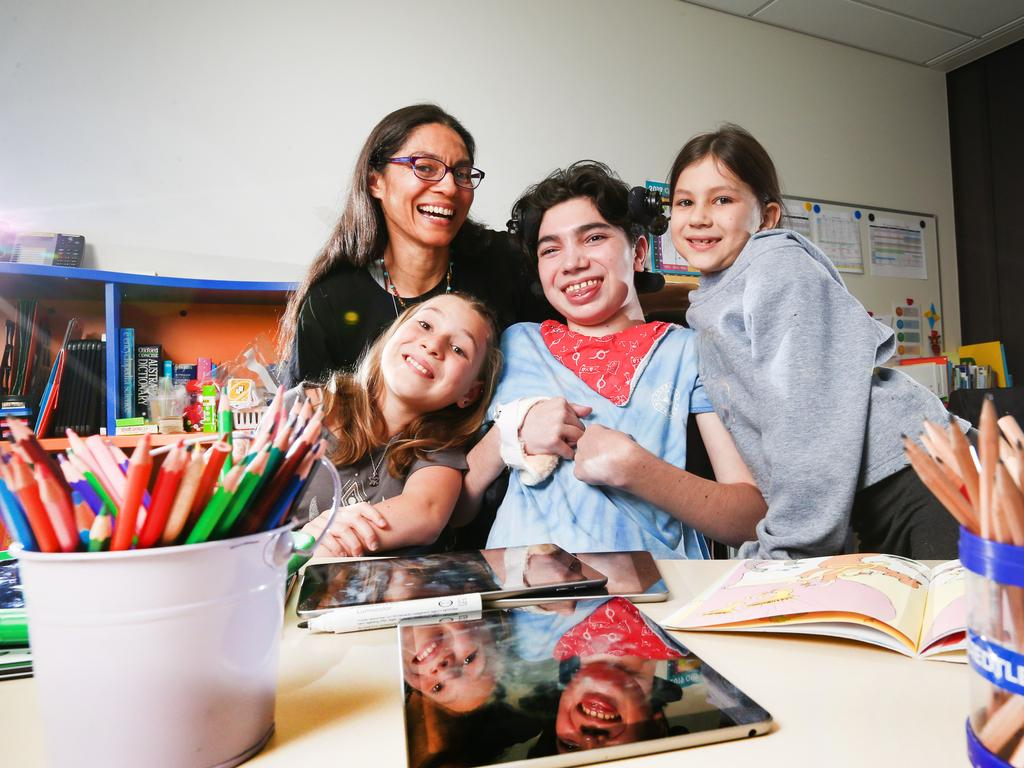 Jarrah Jones, 14, is supported by his siblings Akasha, 11 and Calypso, 8 and mum Nathalie Brouard at the Queensland Children's Hospital where he had been battling Wilson's disease. Picture: NIGEL HALLETT