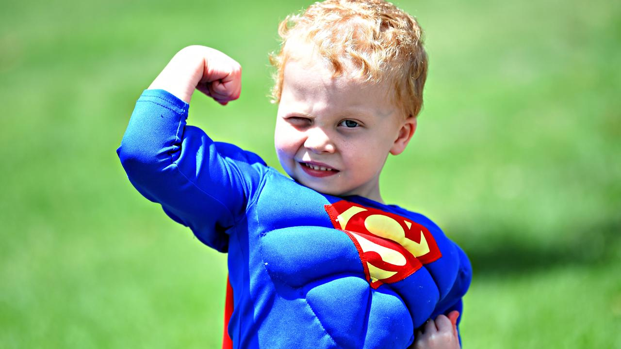 CUTE: Super toddler Liam Gullick, 3, shows off his guns at the Dress Up Day at the Nambour Showgrounds. Photo: Warren Lynam.