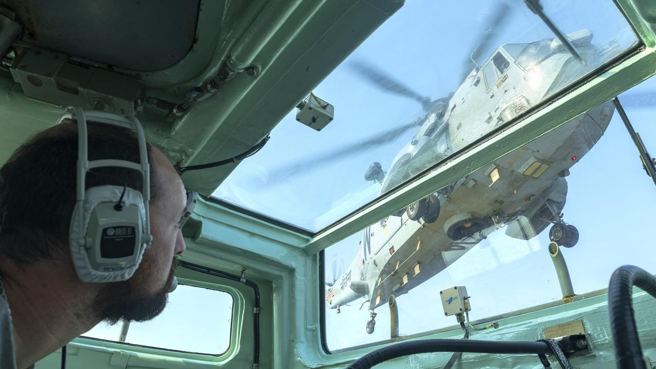 Royal Australian Navy officer Lieutenant Edward Costigan watches as an Indian Navy Sea King helicopter prepares to land on HMAS Parramatta's flight deck earlier this year. Picture: Supplied