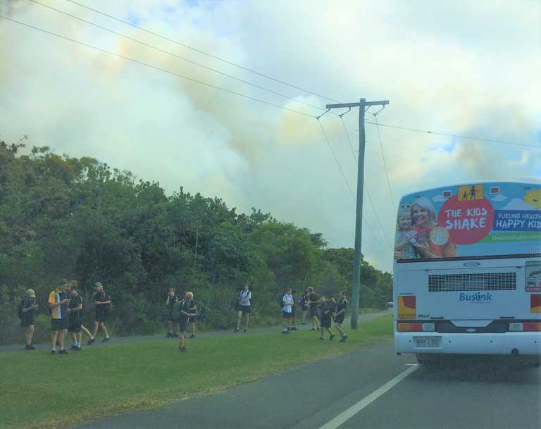 LEFT BEHIND: Coolum High State School students leaving their bus on Wednesday morning during the fire emergency.