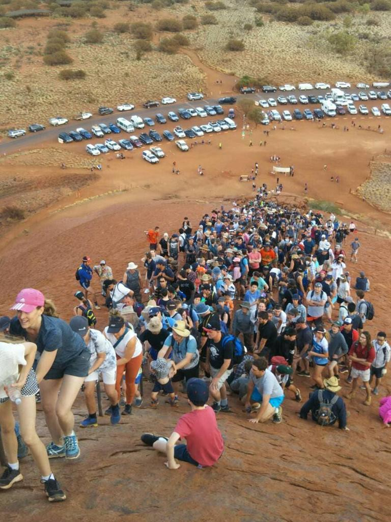 Crowds attempting to climb Uluru.