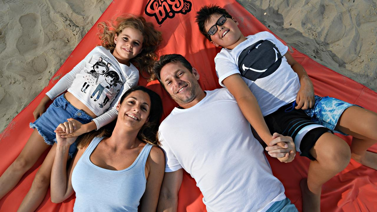 Paul and Nicole Rebeck with their children Bella, 7, and Jake, 8, chill out with the giant beach towel.