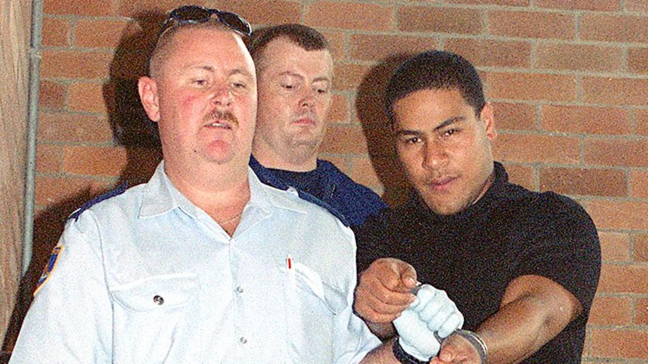 Sione Penisini being led away from court after being charged with the murder of policeman Glenn McEnallay in 2002. Picture: Mick Tsikas.