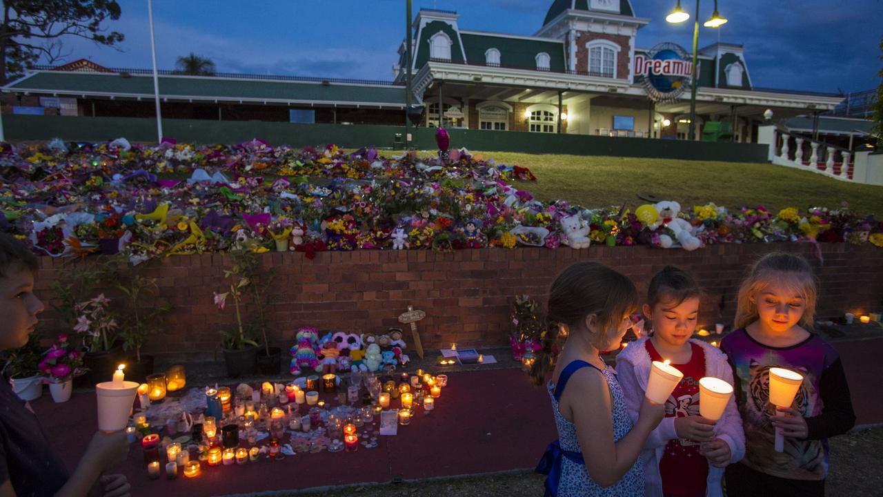 Mourners attend a candlelight vigil outside Dreamworld.