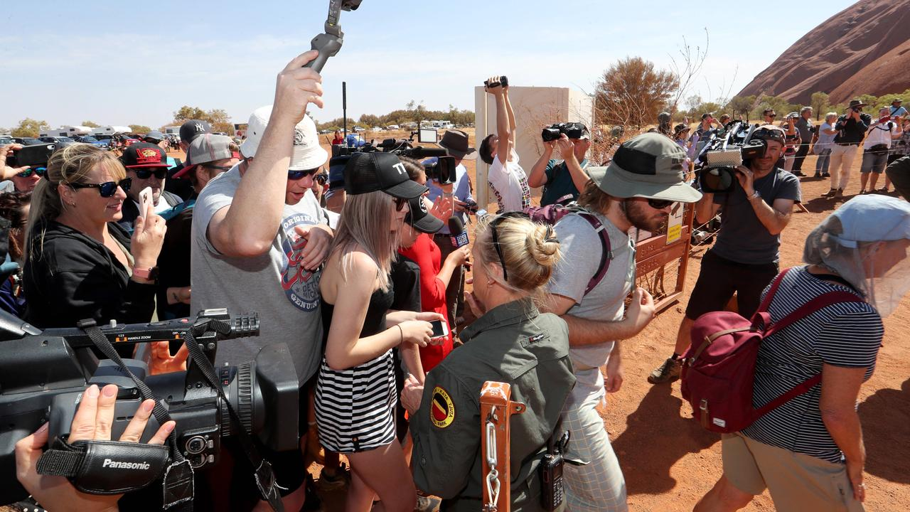 A ranger opens the gate as hundreds of people head up the Uluru climb. Picture: David Geraghty