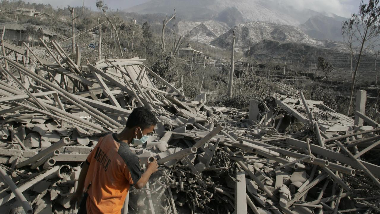 """A rescue worker searches for victims in the debris of """"Ring of Fire"""" volanic eruption."""