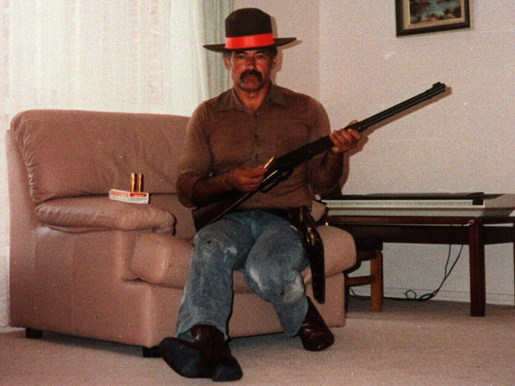 Milat posing for a photo at his home, holding a firearm and wearing a sheriff's badge.