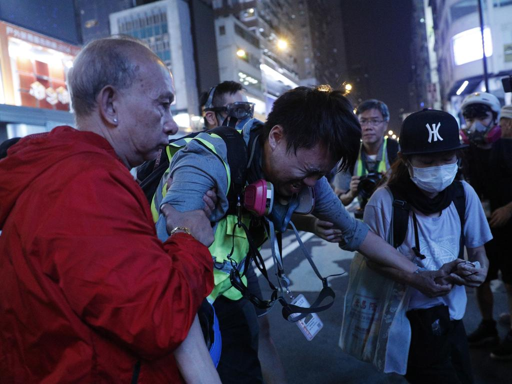 A journalist is assisted after getting hit by pepper spray in Hong Kong. Picture: AP