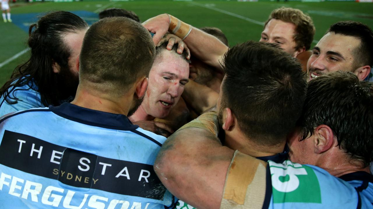 Paul Gallen is mobbed by teammates after winning the series finale in 2016.