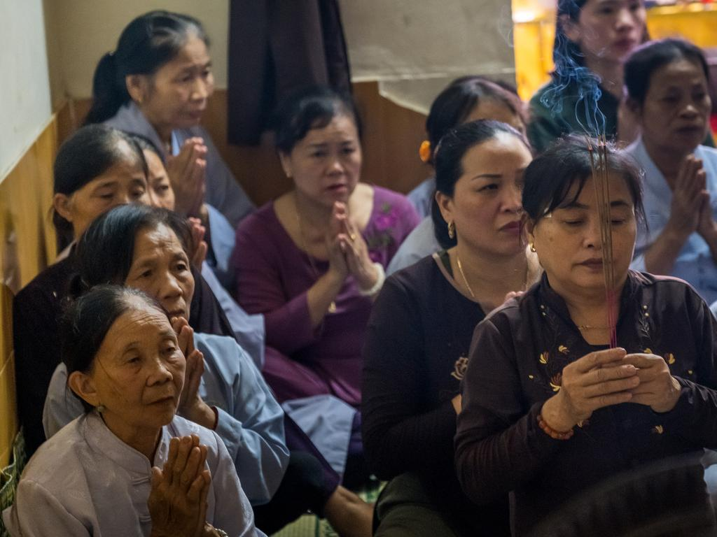 Family members and neighbours of Pham Thi Tra My pray at her house with monks in Vietnam. Picture: Linh Pham/Getty Images.