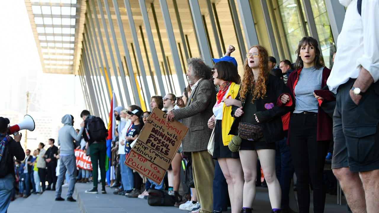 Activists link arms to block an entrance to the Melbourne Exhibition and Convention Centre. Picture: AAP Image/James Ross