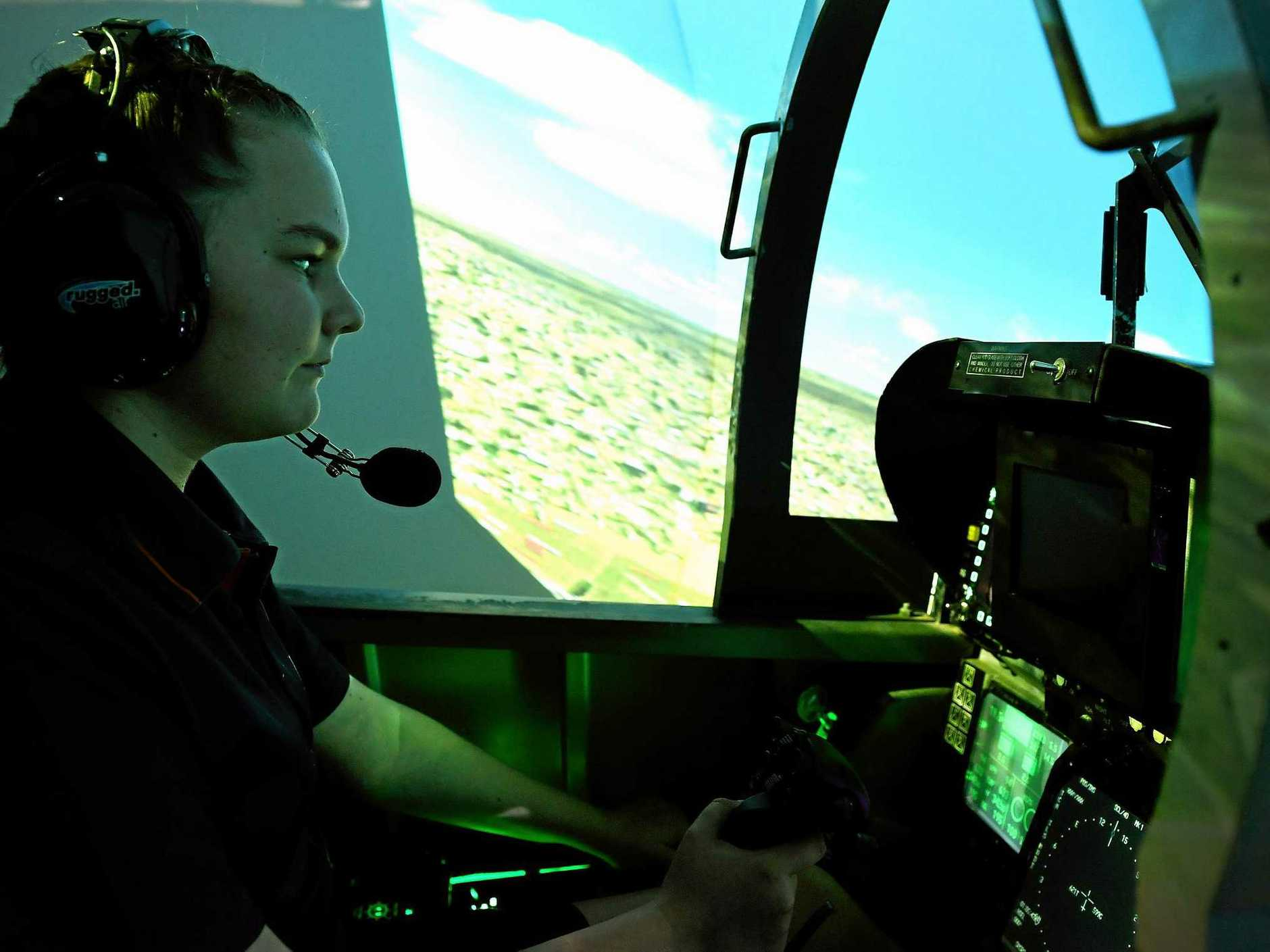 Ballina Coast High School year 8 student Mia Elks participates in the F18 hornett flight simulator.