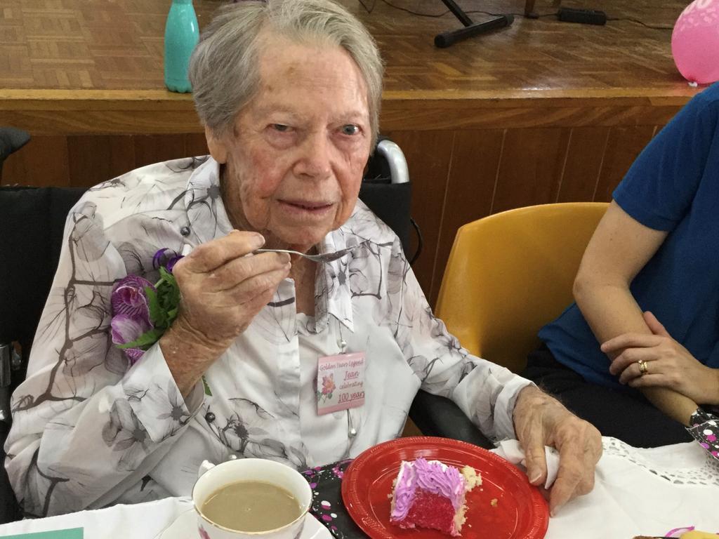 Jean Dray tastes her birthday cake as she celebrates her 100th birthday