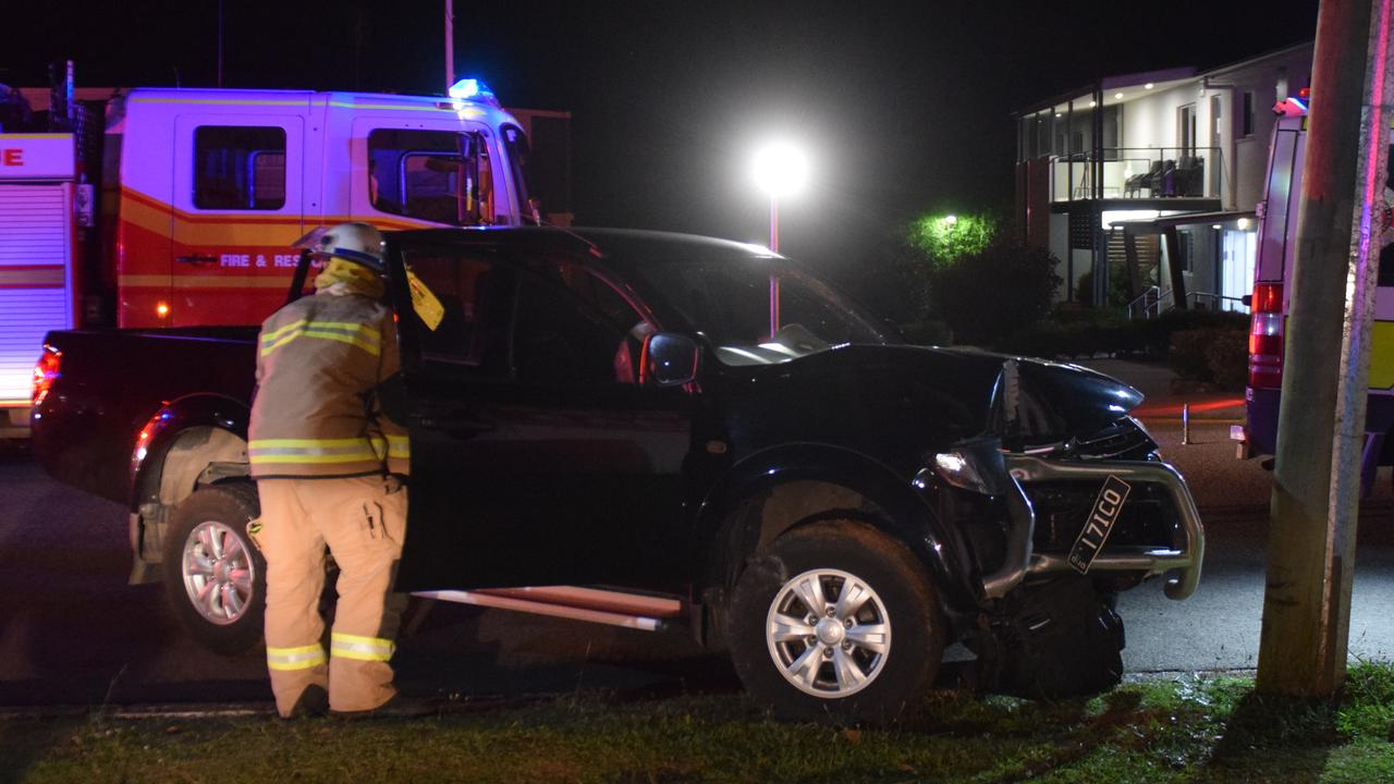 A firefighter inspects a ute after it crashed into a power pole at the intersection of King St and Lavarack Crescent in Buderim.