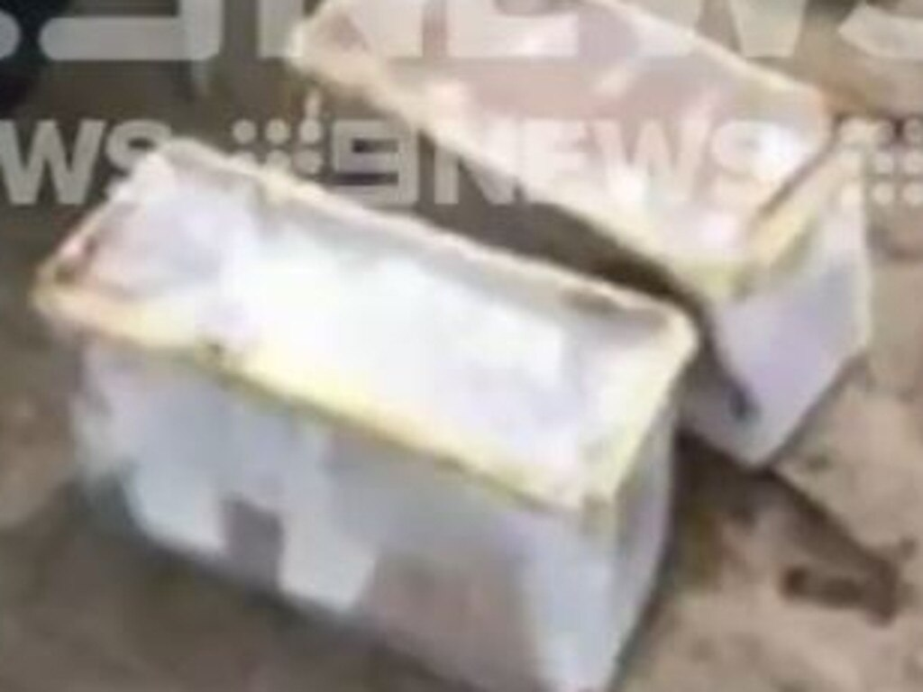 About 200,000 in cash was hidden in several large plastic containers that were buried on the site. Photo: Nine News