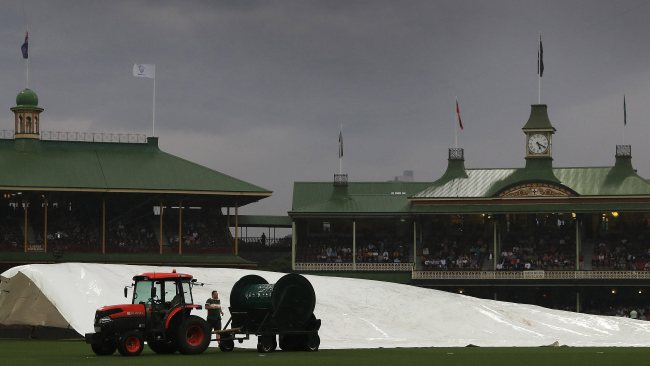 Rain stops play as groundsmen cover the pitch during the International T20 match between Australia and Pakistan at the SCG. Picture: Brett Costello