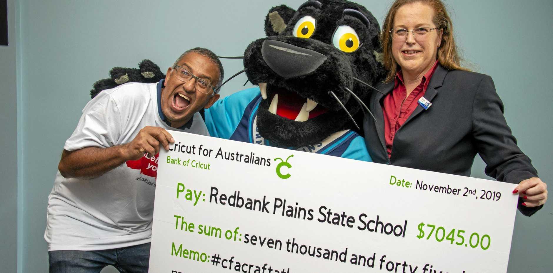 DONATION: Ashish Arora, Cricut CEO, the Redbank Plains State School panther and Pam Coyle, principal.