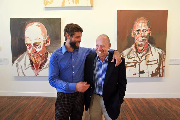 Ben Quilty and Air Commodore John Oddie at the National Art School Gallery in 2013. Quilty's paintings of Oddie hang on the wall behind.