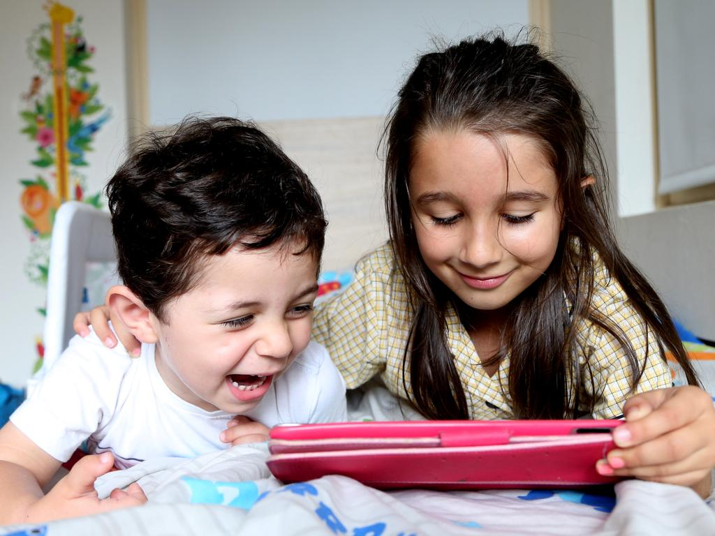Gideon Heik with sister Ariella playing with his iPad under controlled conditions. Picture: Adam Taylor