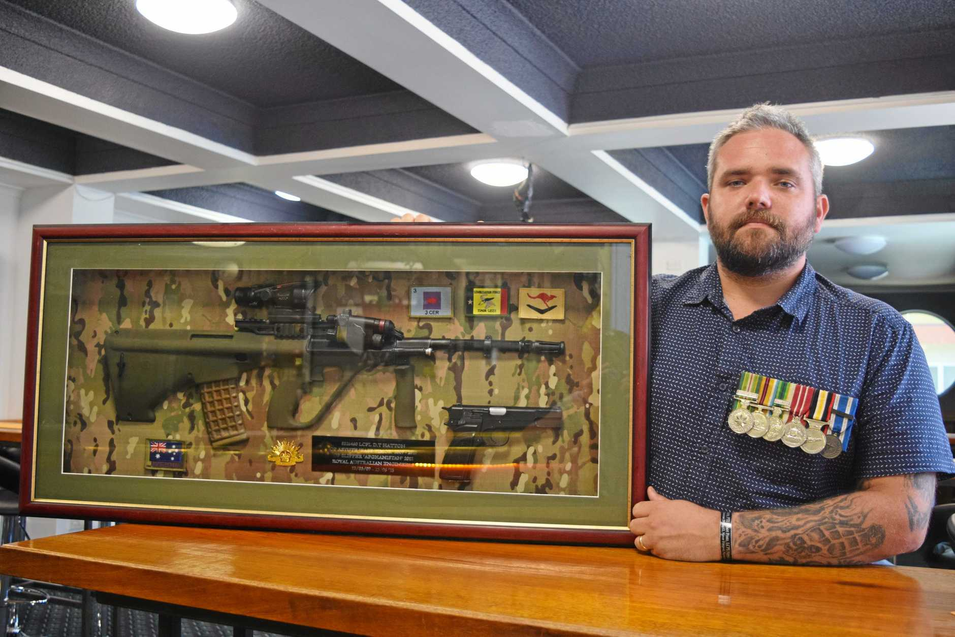 TIME FOR REMEMBRANCE: Veteran Daniel Hatton with a plastic mould of the gun he used while in the Australian Army in Afganistan. It is now on display at Proserpine RSL.
