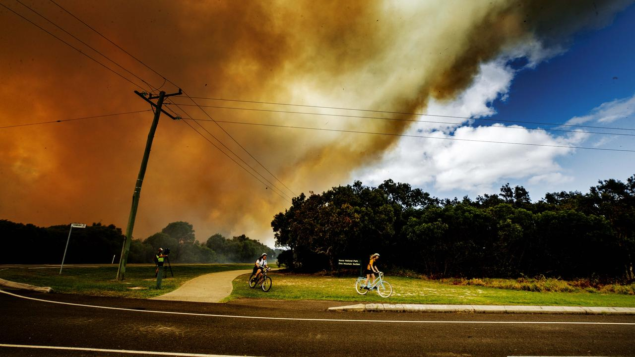 Coolum school kids evacuate on their bikes as a bushfire rages between Coolum and Peregian Beach. Photo Lachie Millard