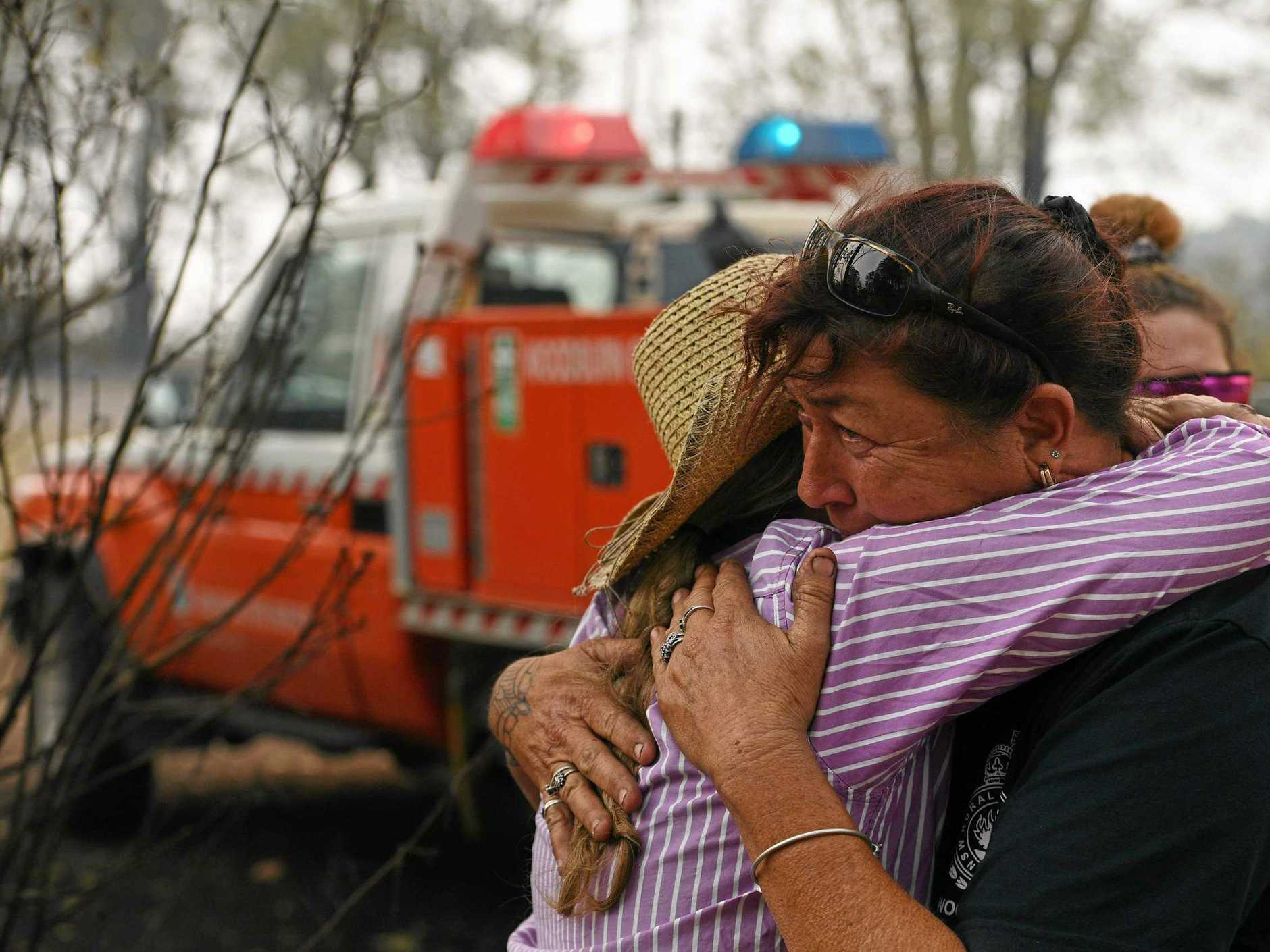 Bora Ridge resident Clare Barry embraces Rural Fire Fighter Raelene Davis after Raelene and her daughter Chantelle helped save the property and horses.