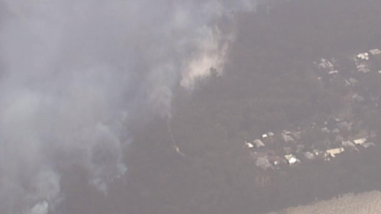 Aerial vision shows a plane dropping water on a fire front near homes on the shores of Lake Cooroibah.