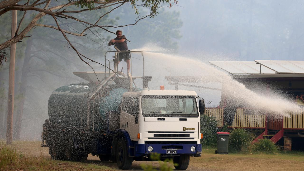 Steve Rhind and his son Joel battle the fires with a water tanker. Picture: Nathan Edwards