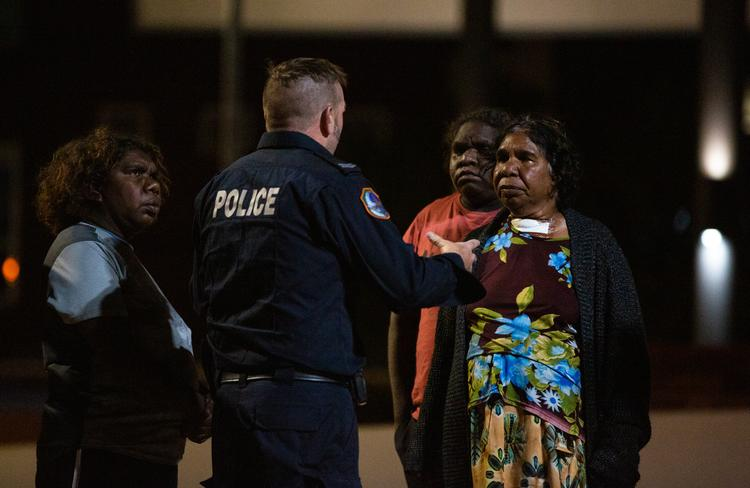 Mr Walker's family question a police officer at the Alice Springs Hospital late on Saturday night, hoping to find out if he was still alive. Picture: EMMA MURRAY