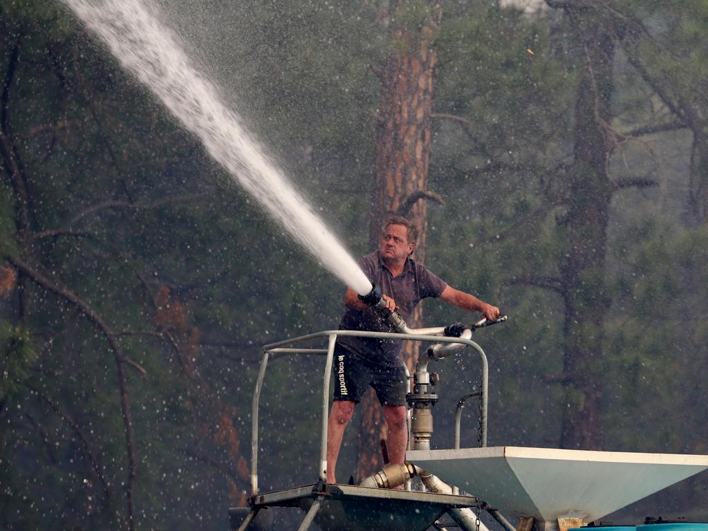 Steve Rhind sprays water from a tanker as a bushfire threatens Johns River on the NSW mid-north coast. Picture: Nathan Edwards